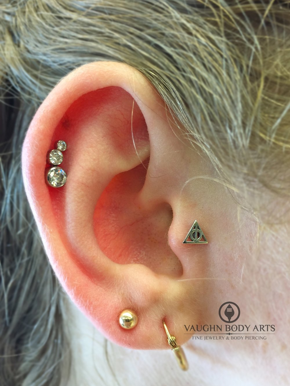 "Tragus piercing featuring a 14k white gold ""Deathly Hallows"" end from BVLA."