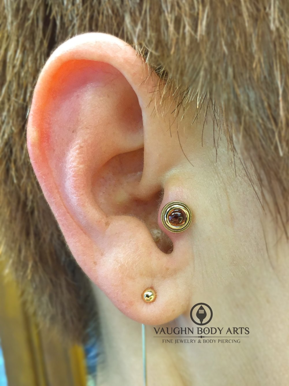"Tragus piercing featuring a 14k yellow gold and genuine garnet ""Millgrain Bezel"" end from BVLA."