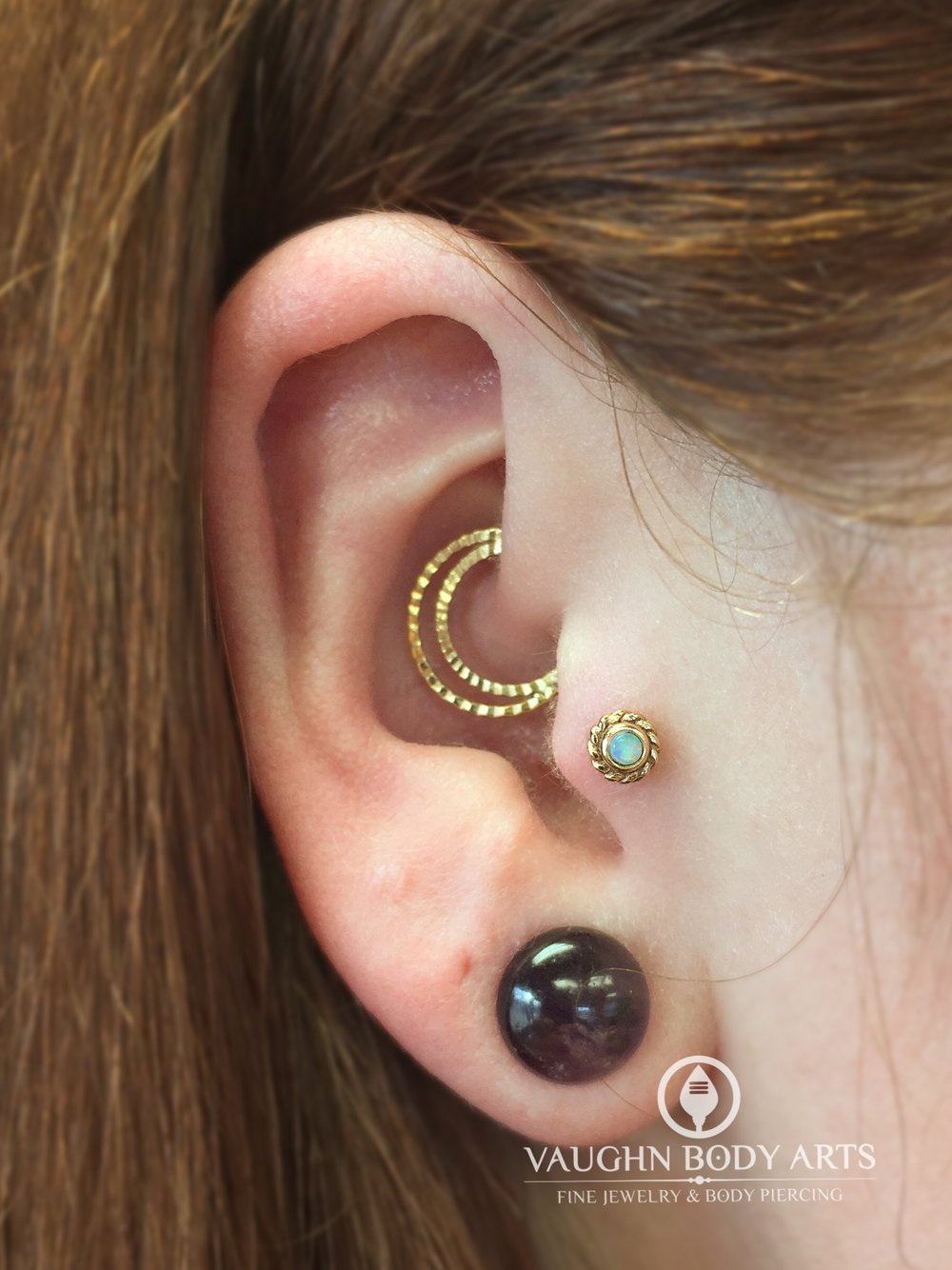 "Tragus piercing with a 14k yellow gold and opal ""Mini Choctaw"" end from BVLA."