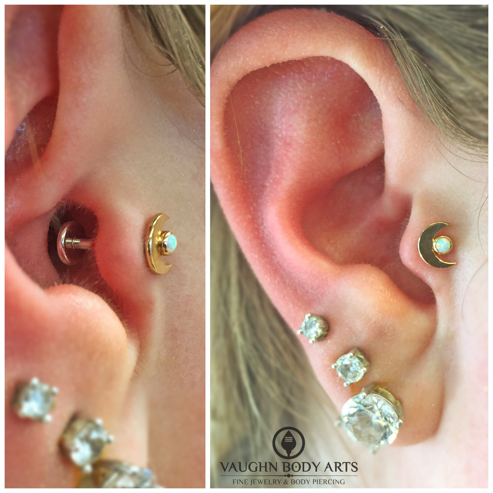 Tragus piercing with an 18k yellow gold and opal crescent moon end from Anatometal.