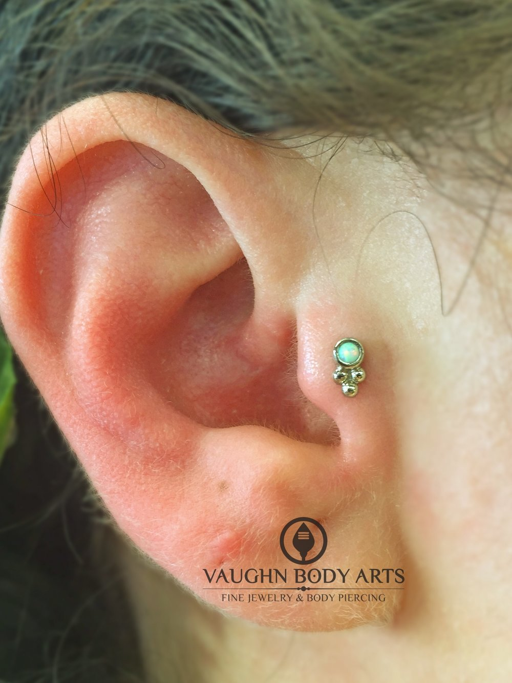 "Tragus piercing with an 18k white gold and opal ""Sabrina"" end from Anatometal."