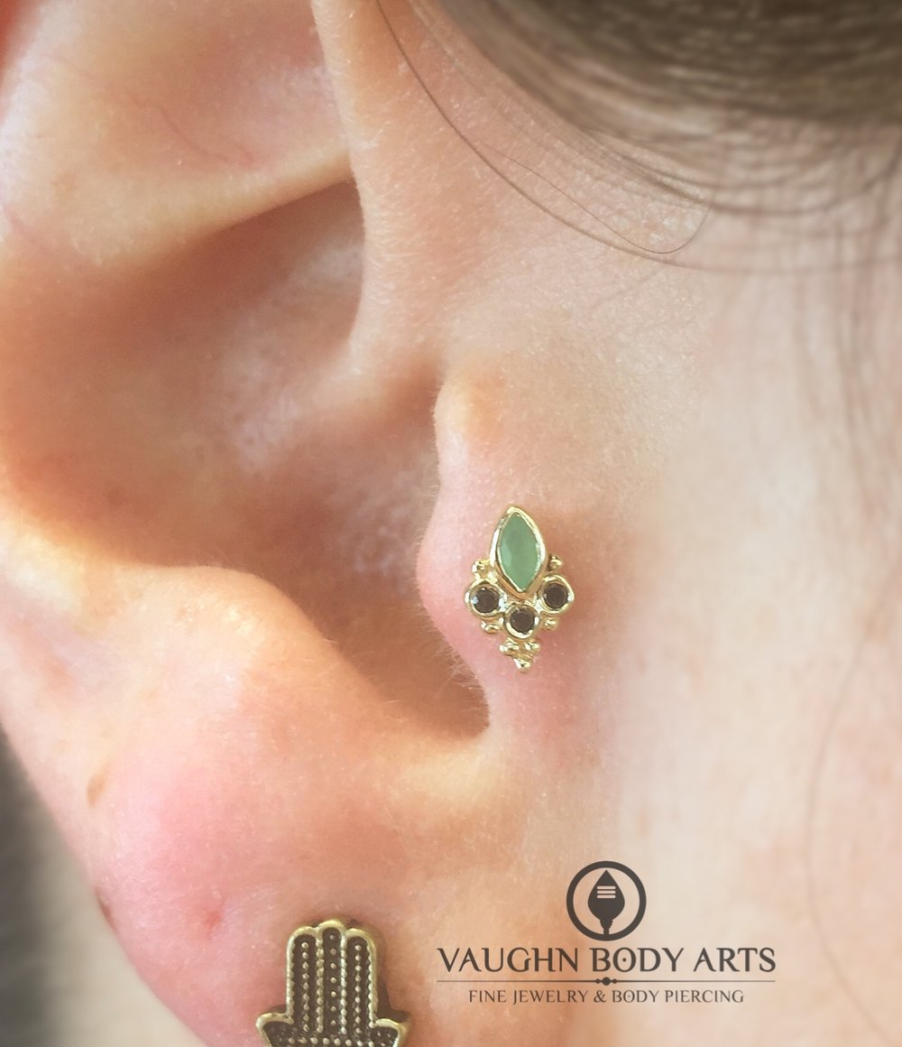 "Tragus piercing featuring a 14k yellow gold ""Marquise Sarai"" with chrysoprase and genuine black diamonds from BVLA."