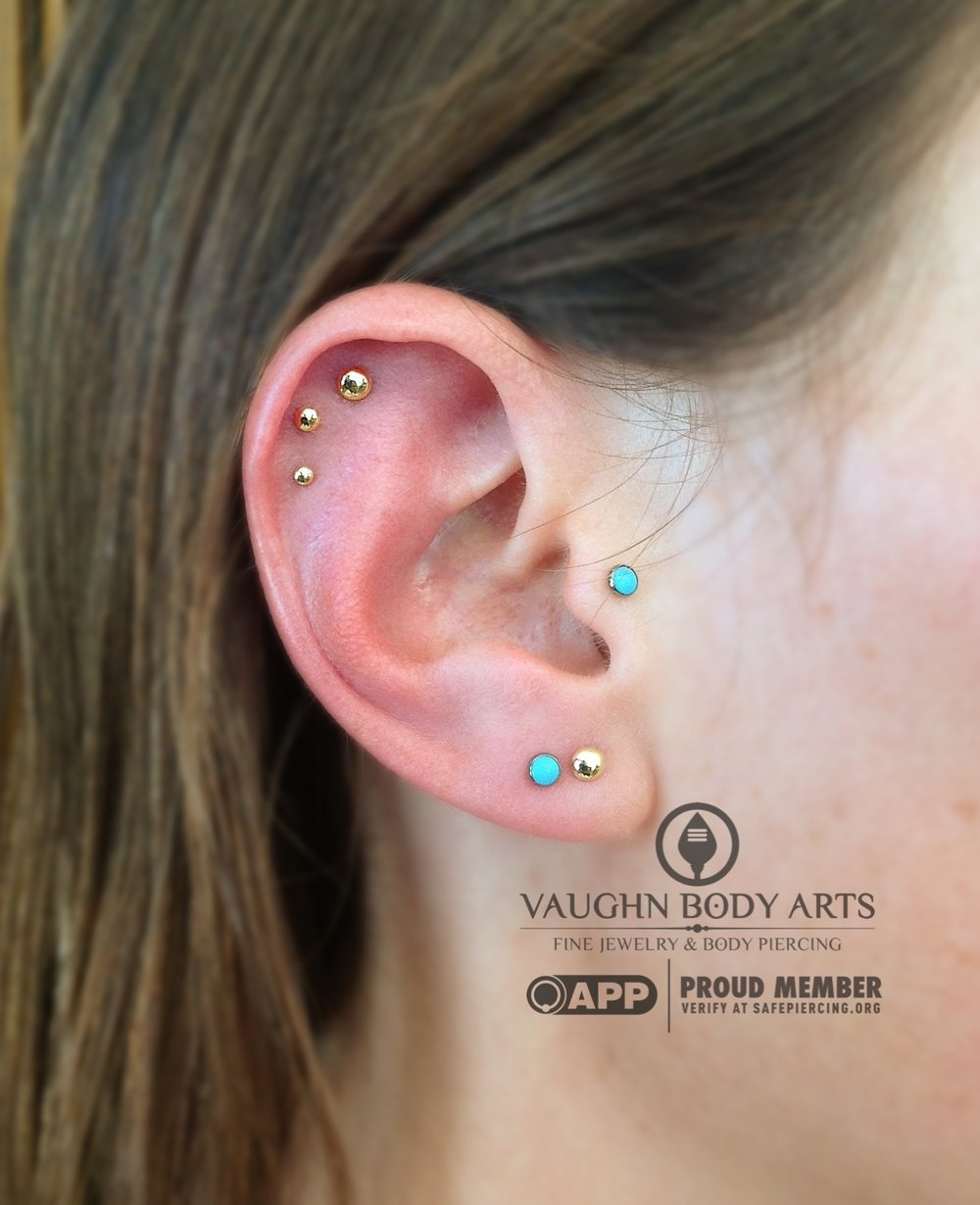 Triple helix piercings featuring 14k yellow gold dome ends from BVLA.