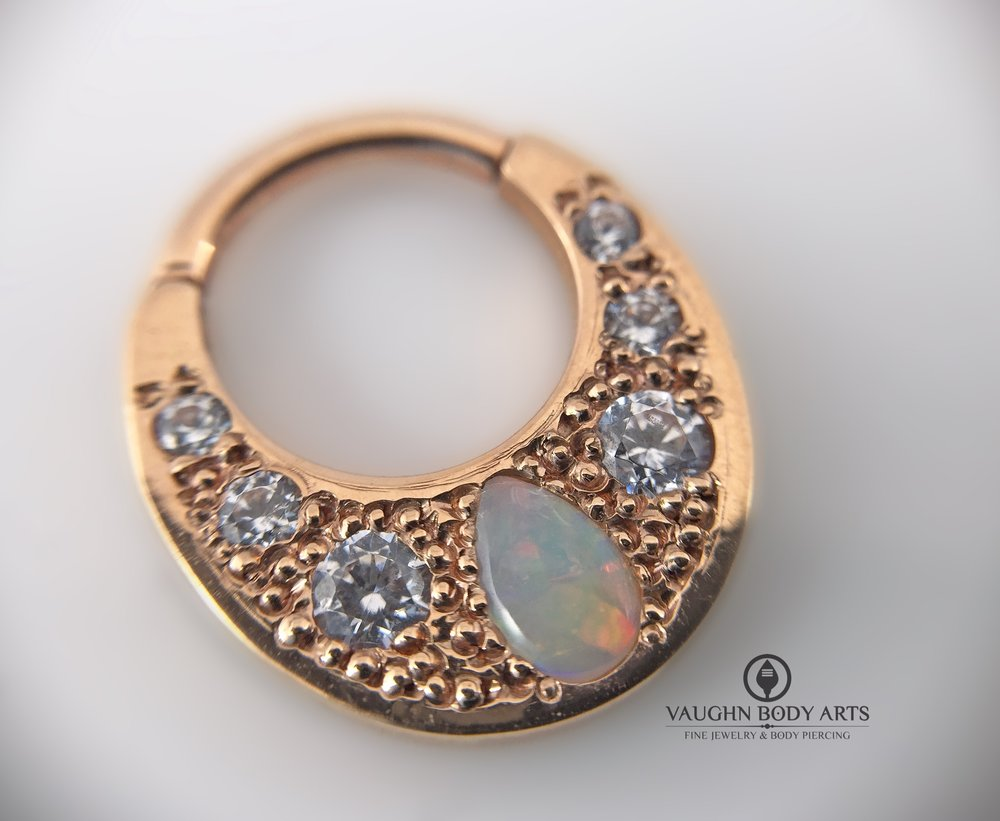 "14k rose gold ""Boston Tiger"" clicker from BVLA featuring clear cz's and a genuine white opal."