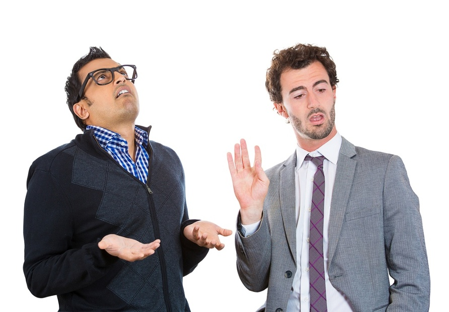 Closeup portrait, annoyed nerd man with black glasses by what a business guy in suit is telling him, talk to hand, isolated white background. Negative human emotion facial expression feelings..jpeg