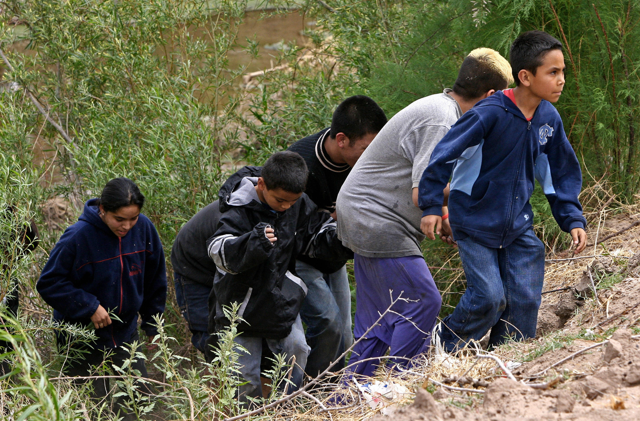 MEXICO-MIGRATION - An entire family emerges from the bushes on the Mexican bank of the Rio Bravo --reduced in that particular point to a narrow stream-- 11 April, 2006 near Ciudad Juarez, Mexico. Thousands of illegal immigrants cross the border to enter the United States every day in search of better opportunities. AFP PHOTO/Omar TORRES (Photo credit should read OMAR TORRES/AFP/Getty Images)