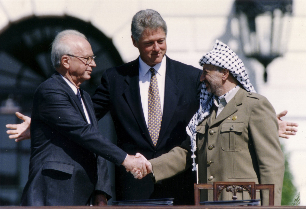 Then PLO Chairman Arafat shakes hands with then Israeli PM Rabin after the signing of the Israeli-PLO peace accord, in Washington