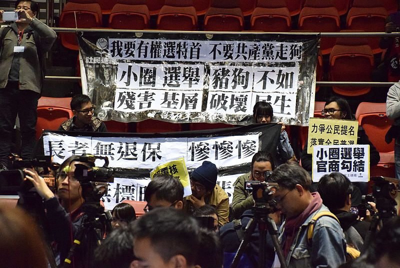 "Protest signs opposing the small circle Chief Executive ""election"" at a journalist's conference after Carrie Lam announced her intention to run. Source:  Wikimedia"
