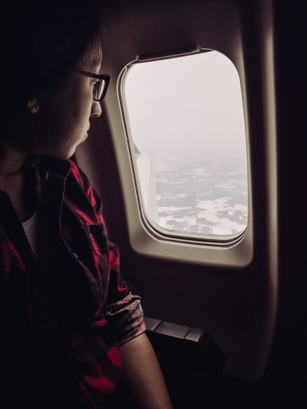 Young woman looking out plane window. JPG