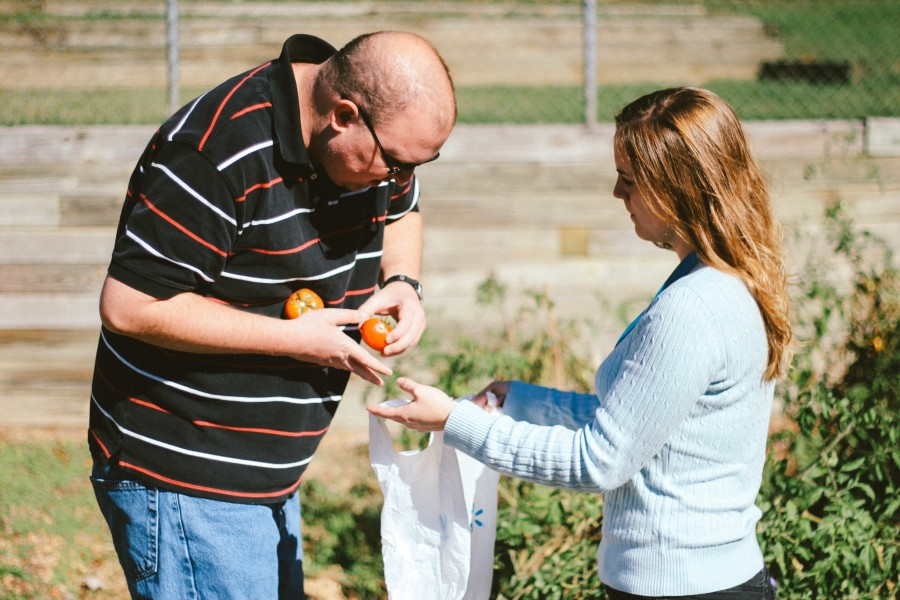 Day Support Supervisor, Brigitte Suijk, QIDP, bags tomatoes with Tom.
