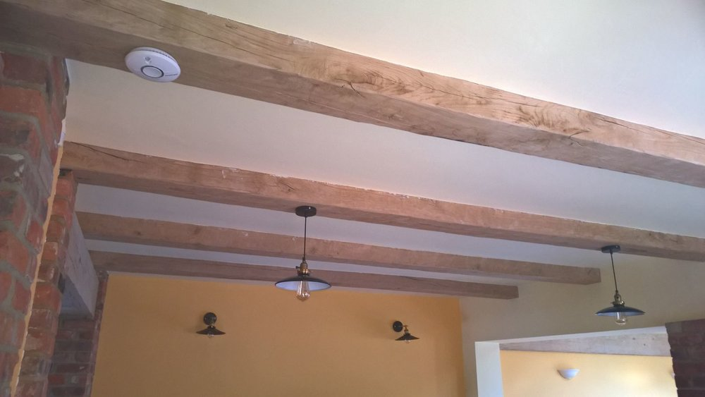 The oak beams finished, waxed, treated and plastered up to