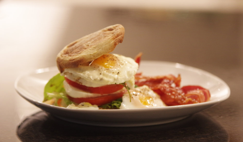 Moz-zilla! - Crispy English muffin, spring lettuce, layers of fresh mozzarella, tomatoes, and basil, and topped with oven-baked, runny eggs.