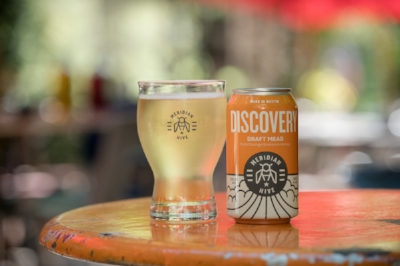 A Can of Discovery next to a Poured Glass of fresh cold Discovery