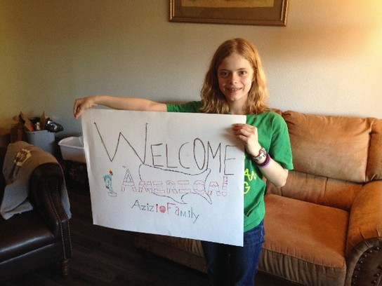 Bridget, one of the young members of Merinda's Welcome Team, shows off a sign she made to welcome the Azizi family to Texas.