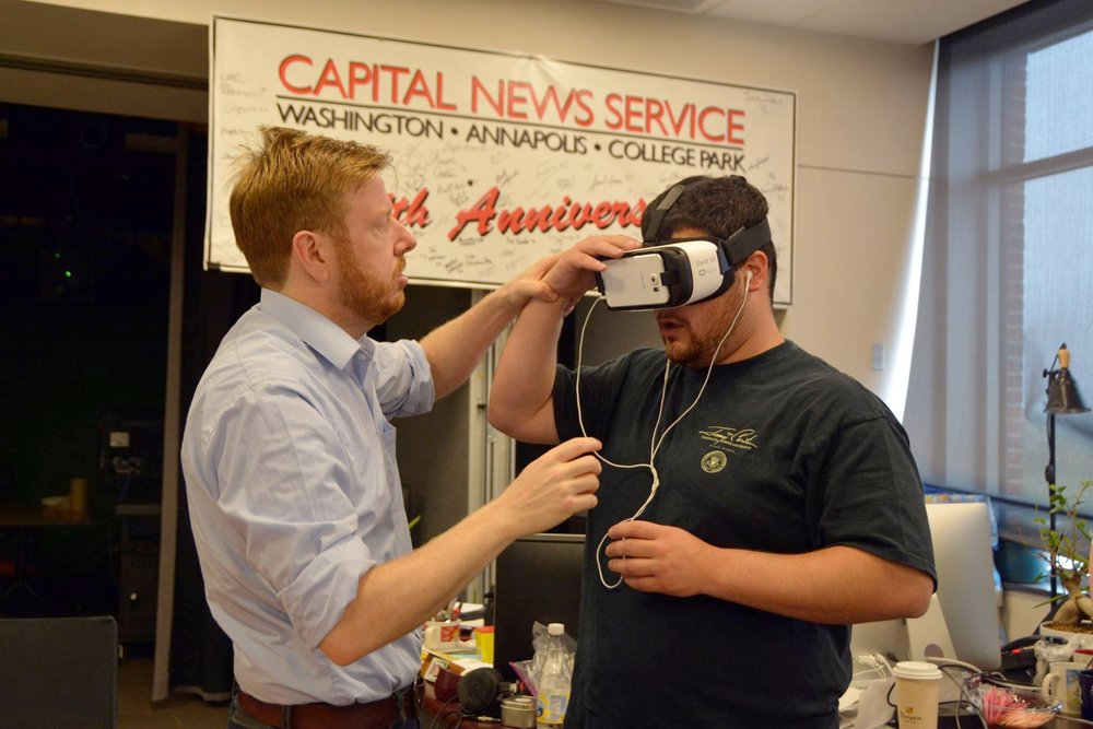 Capital News Service digital director Sean Mussenden demonstrates a VR headset with one of his students.