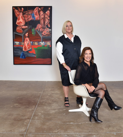"""Wendy Olsoff (sitting) and Penny Pilkington (standing), 2017, in front of David Wojnarowicz's """"North/South: The New Legionnaires"""" (1986, acrylic and printed paper collage on Masonite), at P.P.O.W."""