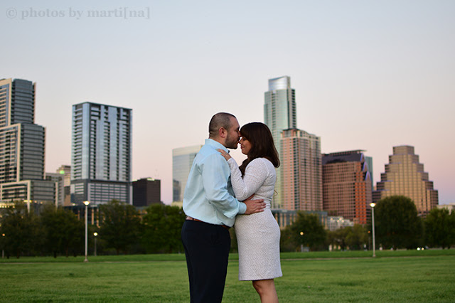 Engaged couple standing in front of downtown Austin, Texas.