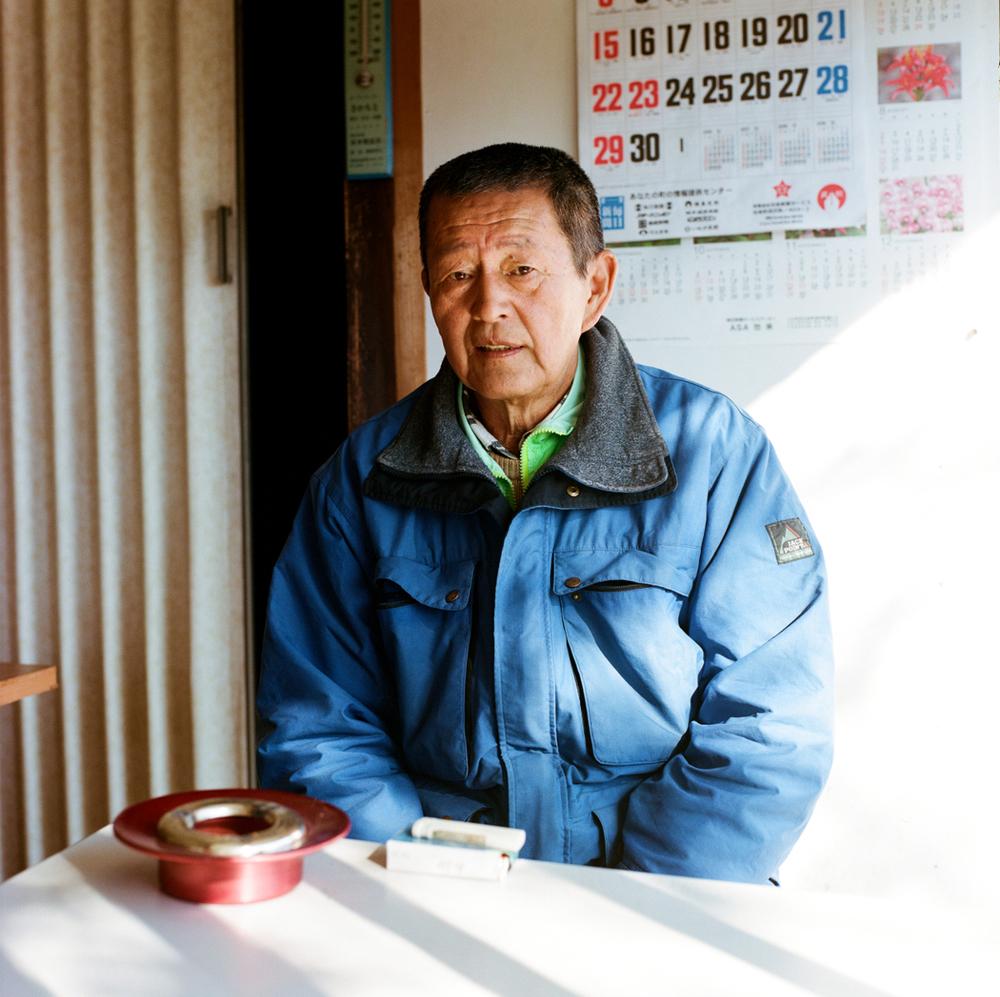 Ce monsieur est revenu dans sa maison, dans l'ancien village de Kido. Il tient un kiosque à journaux avec sa soeur. Avant la catastrophe, il vendait plus de 800 journaux par jour, aujourd'hui moins d'une centaine. Sa maison a subi beaucoup de dégâts à la suite du tremblement de terre et il a dû faire environ 100 000 $ de travaux de rénovation.