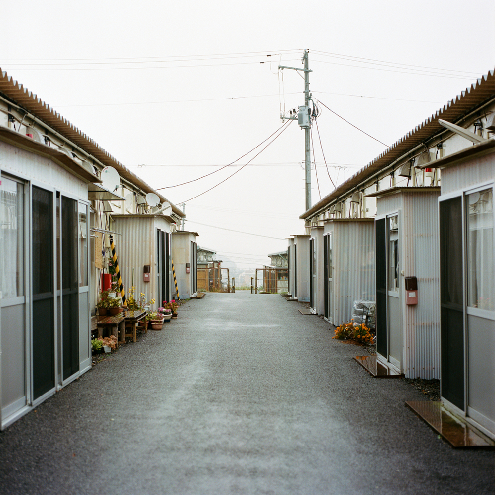 5967 refugees from Naraha still live in Iwaki, which represents approximately 80% of Naraha's official population. 42% of these refugees still live in one of the 13 temporary camps such as Kamiarakawa (the largest). The rest live in apartments. The Kamiarakawa camp, as with all the temporary camps that have been set up after the disaster in Japan, and particularly in Fukushima, consists of a row of regularly spaced prefabricated site bungalows. The living spaces are inadequate, and are often much smaller than the former dwellings of those who were relocated here.