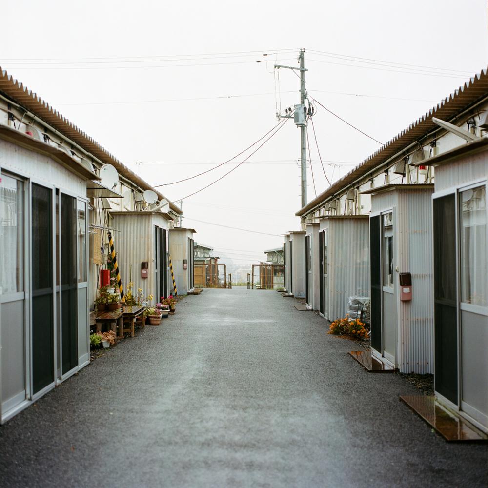 5967人の楢葉町出身の避難者が現在もいわき市に住んでおり、その数は楢葉町の公式人口の約80%を占めています。これらの避難者の42%が上荒川仮設住宅のような13か所の仮設住宅の1つに住んでおり、上荒川のものが最大規模です。他の避難者はアパートで暮らしています。上荒川仮設住宅は、規則的な間隔を空けて並んだ工事現場のようなプレハブ住宅から成っています。これは震災発生後、主に福島県に設置された他の仮設住宅と同じ作りです。居住可能面積は小さく、たいていの場合は避難前に住んでいた家よりもずっと狭いのです。