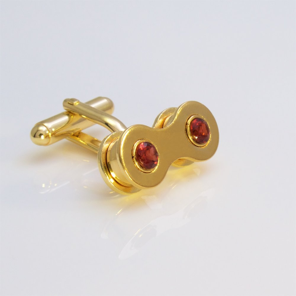A gold bike chain link cufflink with Mozambique garnet.