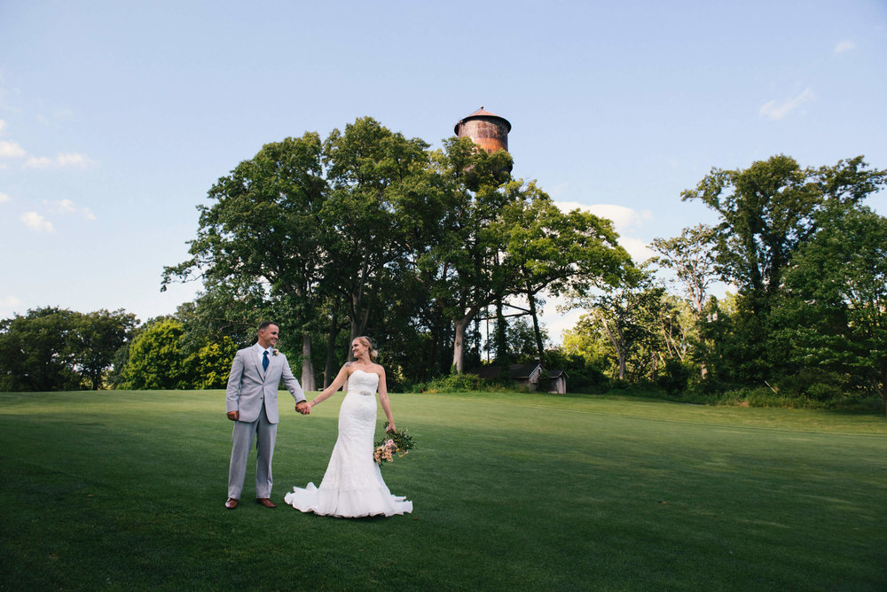 Ashley + Hayden - Who doesn't love an outdoor ceremony featuring a romantic, draped cloth arch? This couple didn't miss a detail from their wedding cake to the popcorn and donut bar to the bride's sparkly shoes.
