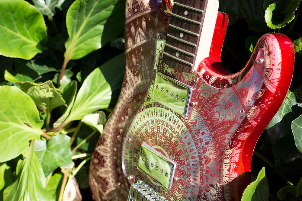 Burntaxe red Mindy Stratocaster in bushes in Brighton Pavilion on first day of Autumn showing a red and mirrored scratchplate