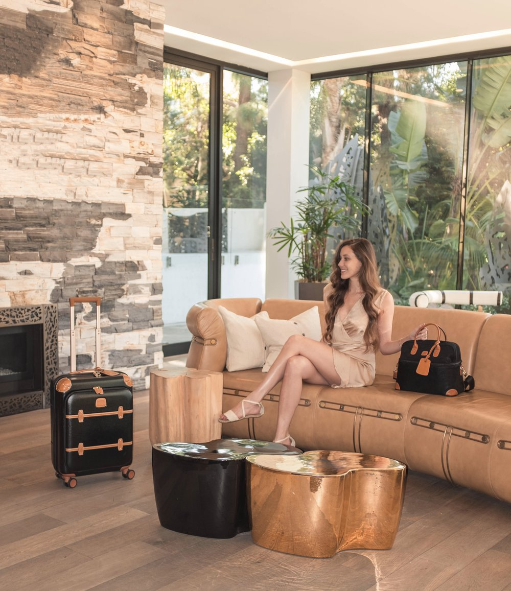 "Carina Otero shown with the BRIC's MILANO Bellagio business v2.0 21"" carry-on spinner (Left) and life tuscan train case (right). Giveaway contestants can enter to win the bellagio business v2.0 21"" carry-on spinner"