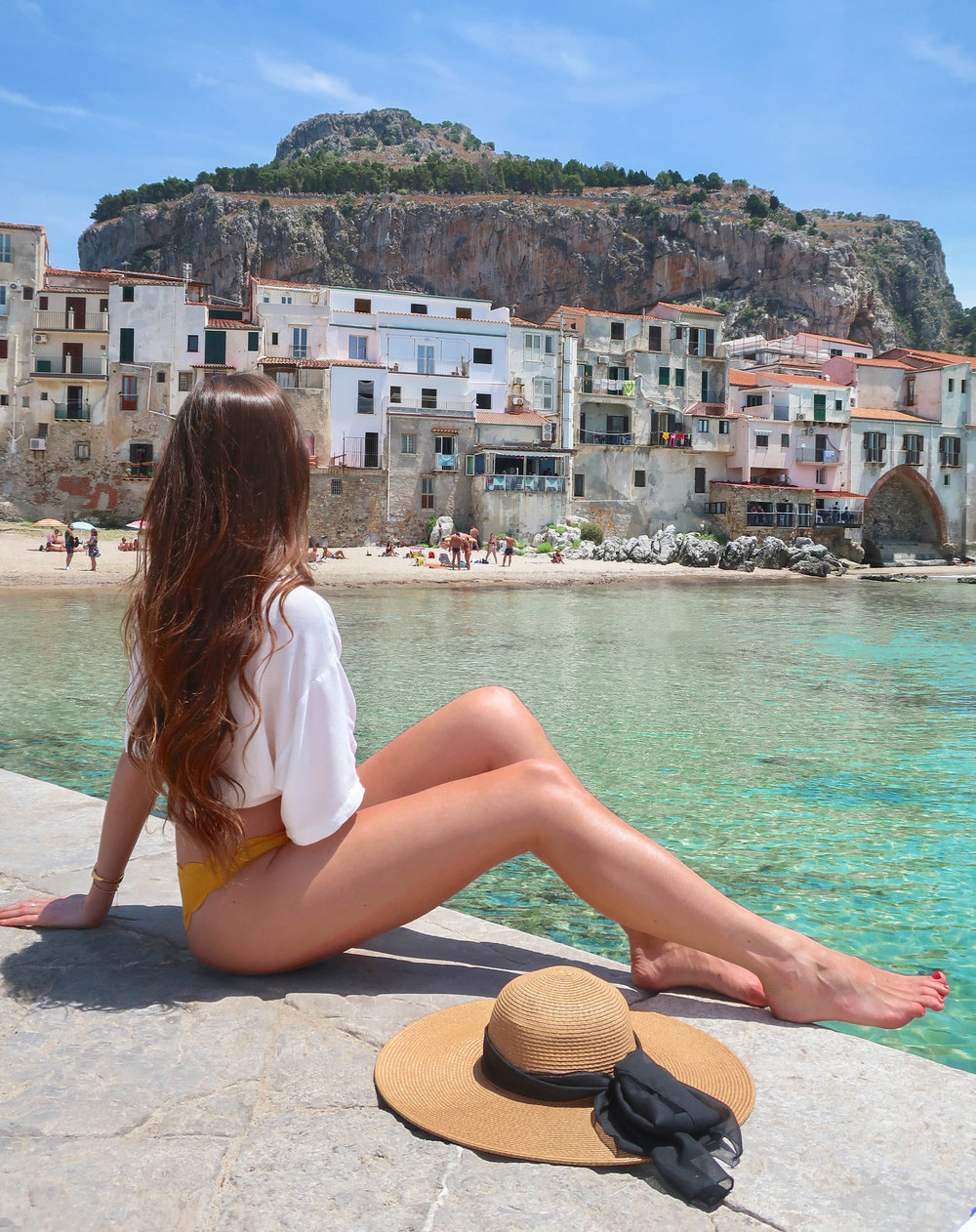 The sicilian town of cefalù is a popular beach amongst travelers and local italians alike.