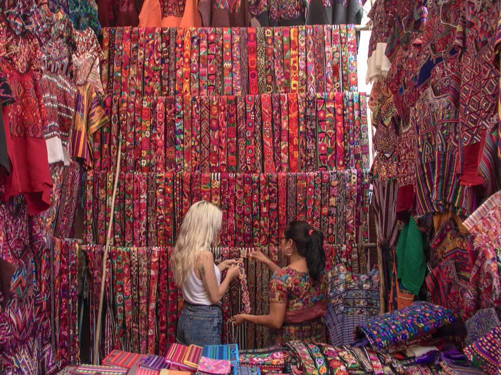 Alyssa and Hiptipico Artisan Director Marleny choose traditional fajas at the Chichicastenango Market in Guatemala