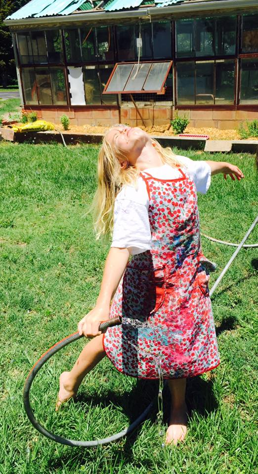SUmmer 2016, Farm GIrl Camp Participant freely enjoying the water hose and the grass on her bare feet