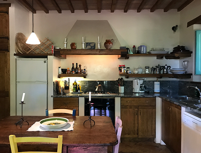Our kitchen for the week (notice the four espresso makers on the shelf).