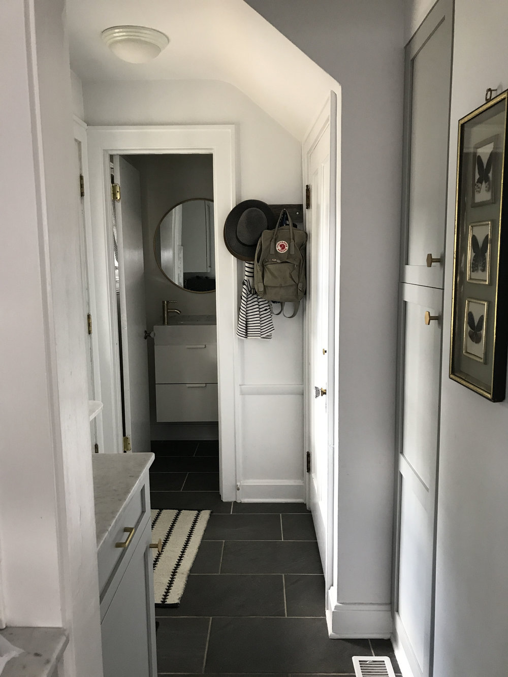 "In this photo, you can see the tiny bath across the back entry. photo was taken from kitchen. This entire zone shares a black tile floor and all ultimately need to ""play nice"" together."