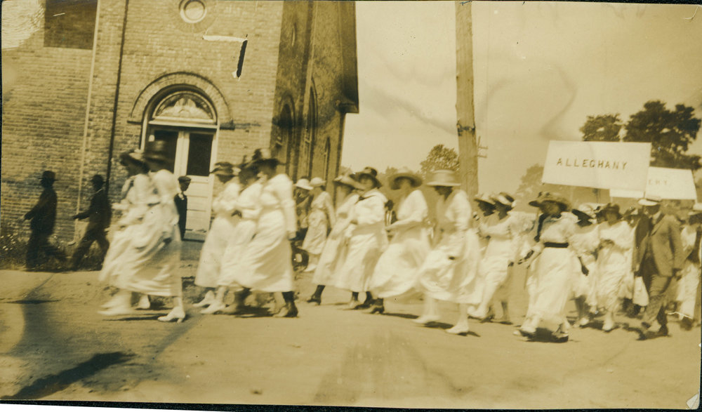 "Women marching in the July 4, 1919, parade through Boone turn right from West King St. (then known as ""Main Street"") onto today's College Street in front of the First Baptist Church (built 1916, demolished 1936). Image courtesy of the H. L. and Gladys Coffey Collection, Digital Watauga Project."