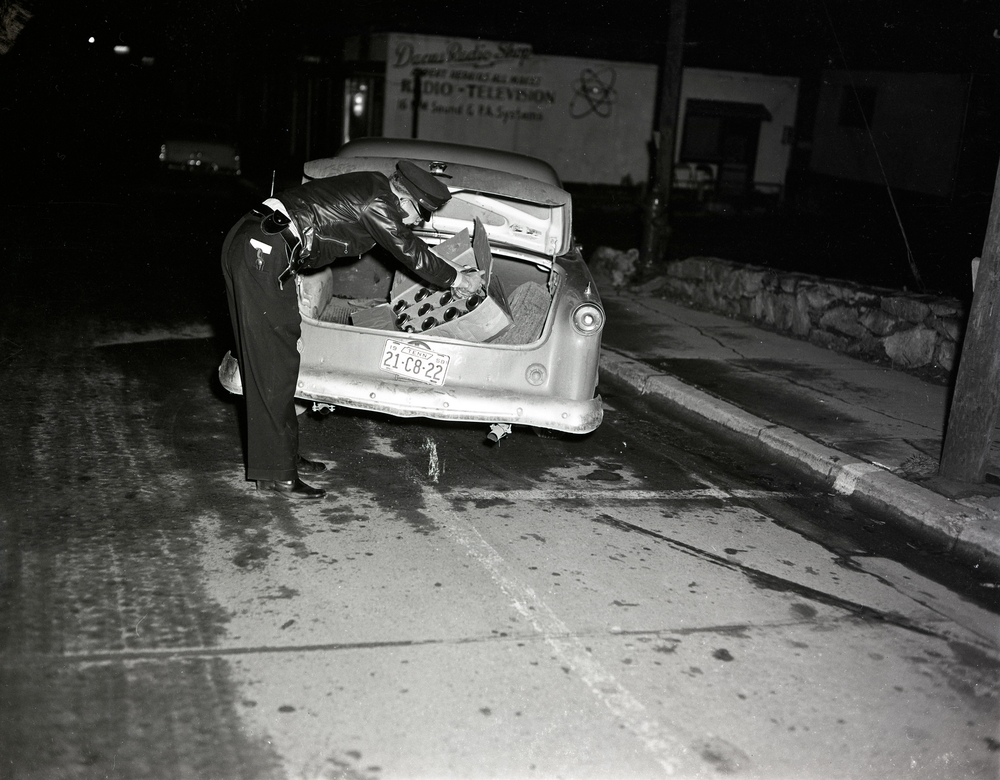 A police officer on the streets of Boone searches a box of jars with clear liquid found in the trunk of a car licensed in Tennessee (date unknown, but probably early 1957). The Dacus Radio Shop is visible in the background. Image is from the forthcoming Palmer Blair Collection, Digital Watauga Project.
