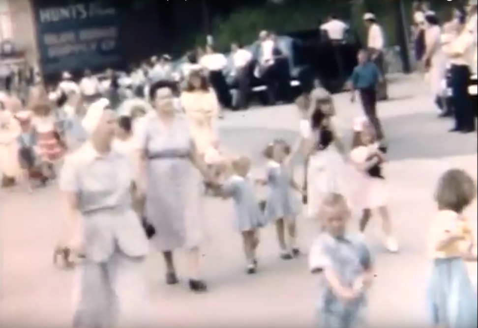 Screenshot from the Clarence A. Price Home Movies showing young girls carrying live cats in the 1949 Watauga County Centennial Parade as they pass in front of the Jones House on West King Street in Boone, NC.