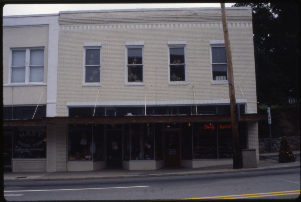 The W. R. Winkler Building (1927) endured the indignity of having its brick painted and an ill-suited, cable-hung awning applied during the middle period of its architectural history. Seen here in the 1990s, the building originally had a double-entrance configuration. Mast General Store later reconfigured the two entrances into one, removed the paint from the brick, and removed the cable-hung awning. Image courtesy of the Downtown Boone Development Association Collection (Dow-Boo-1-058), Digital Watauga Project.