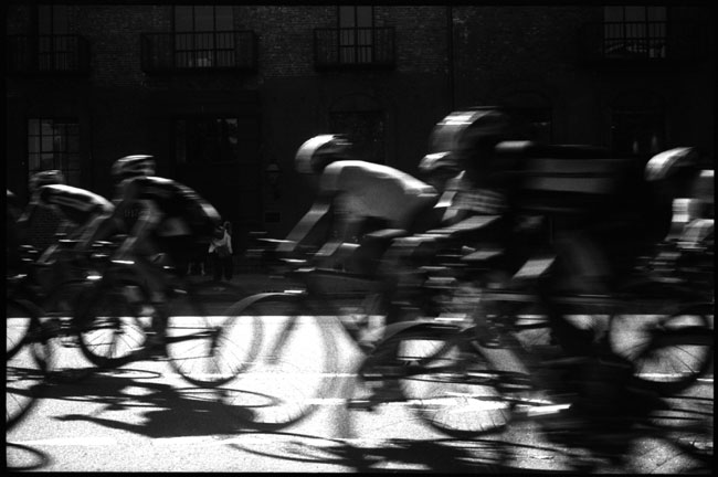 black and white photograph: cyclists, front street, san francisco