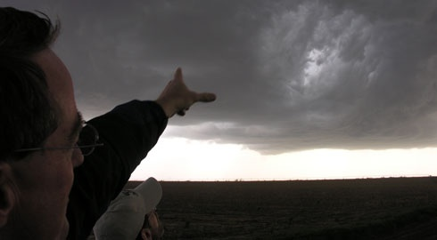 Roger Hill, of Silver Lining Tours, points toward a developing supercell thunderstorm during a 2007 tour. Photo by Laura Bly, courtesy USA TODAY