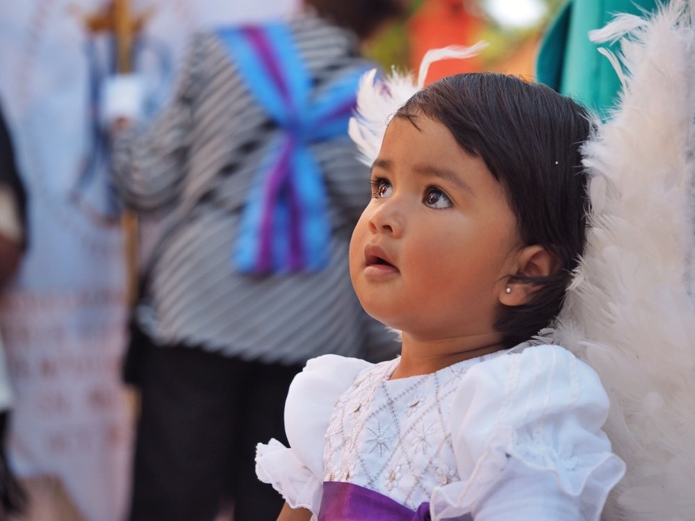 An angelic little girl prepares for a Semana Santa (Holy Week) parade at San Miguel's San Juan de Dios church