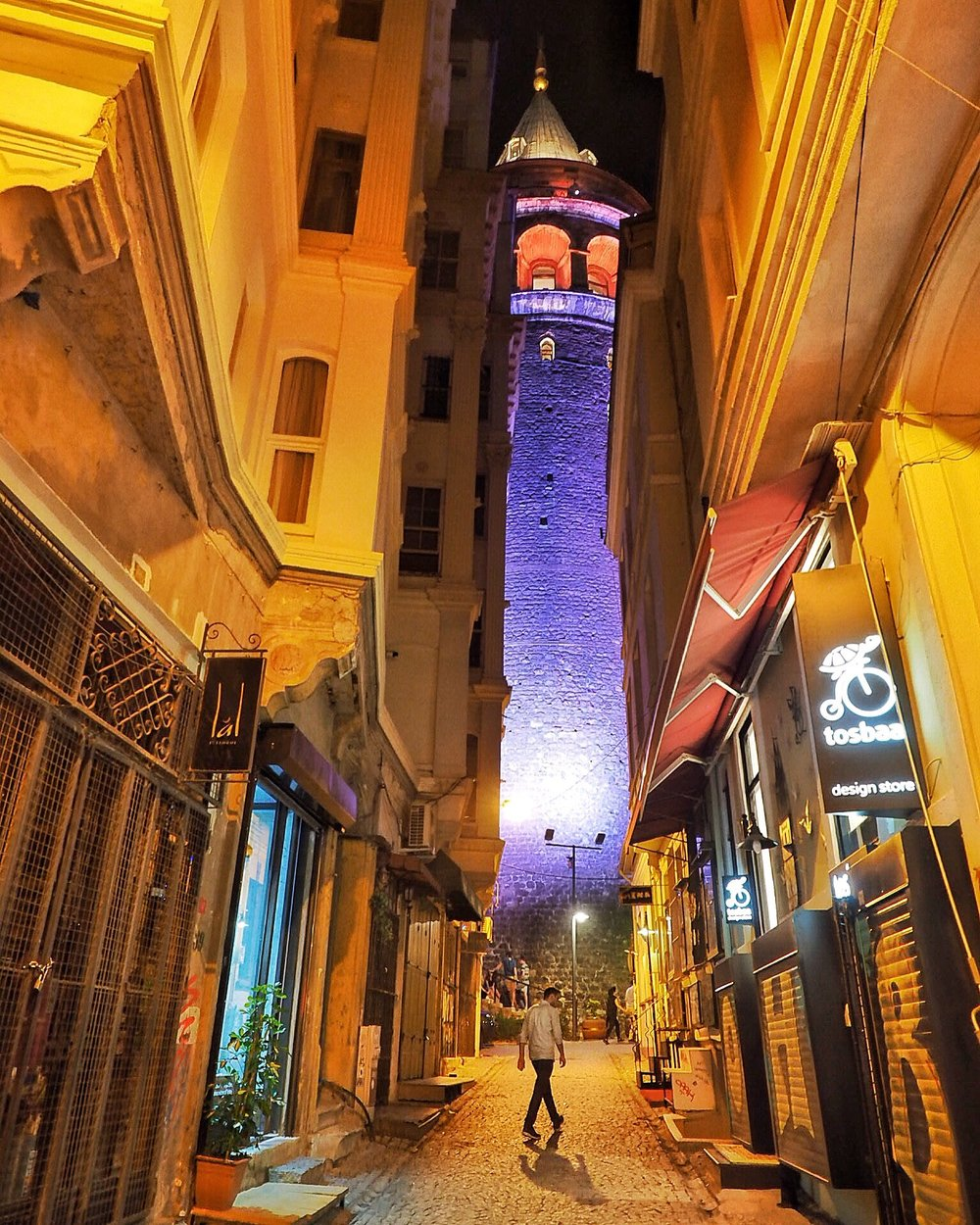 A visitor strolls along a nearly empty street beneath Istanbul's ancient Galata Tower. (Photo by Laura Bly)