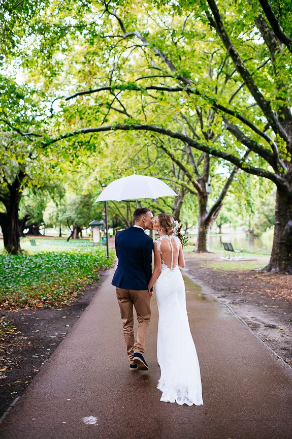20-Ellen_and_Marcus_walking_in_the_park_with_white_umbrella_from_Very_Nice_Classics_wedding_cars_in_Perth.jpg