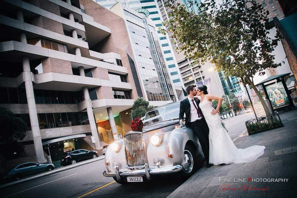 FineLine-Photography-Nicole-and-Peter-leaning-on-Very-Nice-Classics-wedding-car.jpg