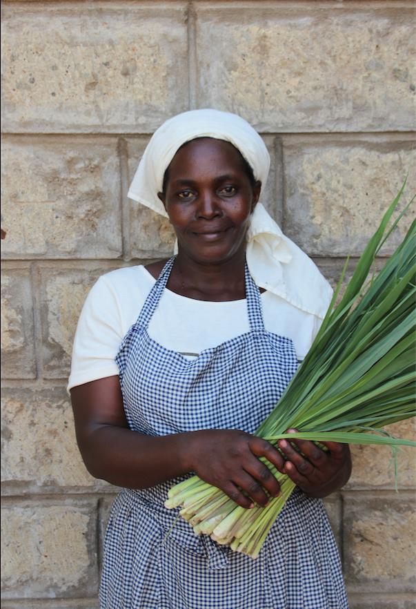 Isabella from the Women's Herbal Tea Co-Op is holding fresh, hand-cut, Organic Lemongrass.jpg.png
