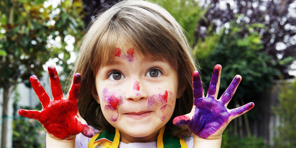 Girl smiling with paint on hands