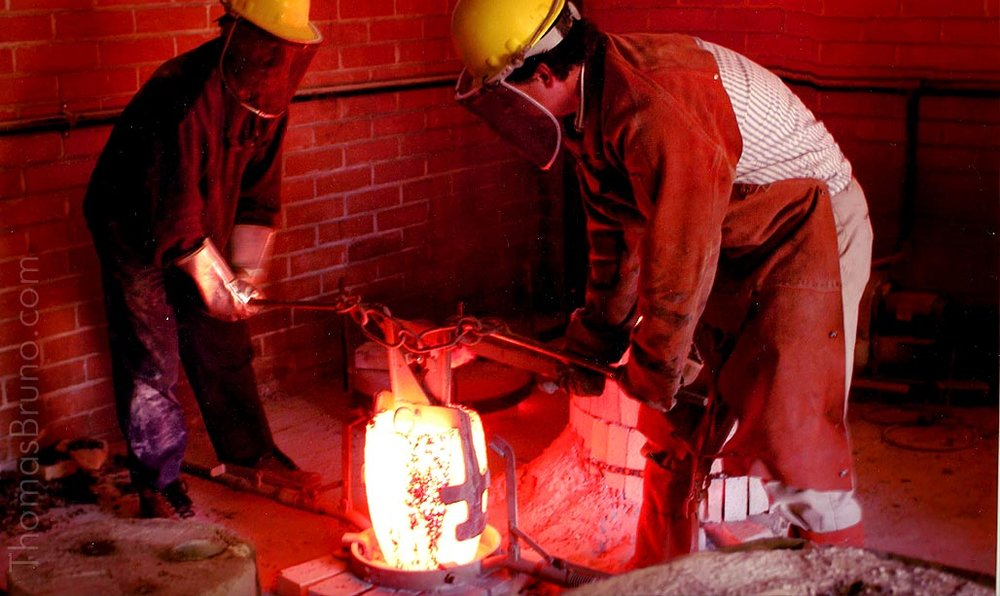 Pouring bronze in the foundry.