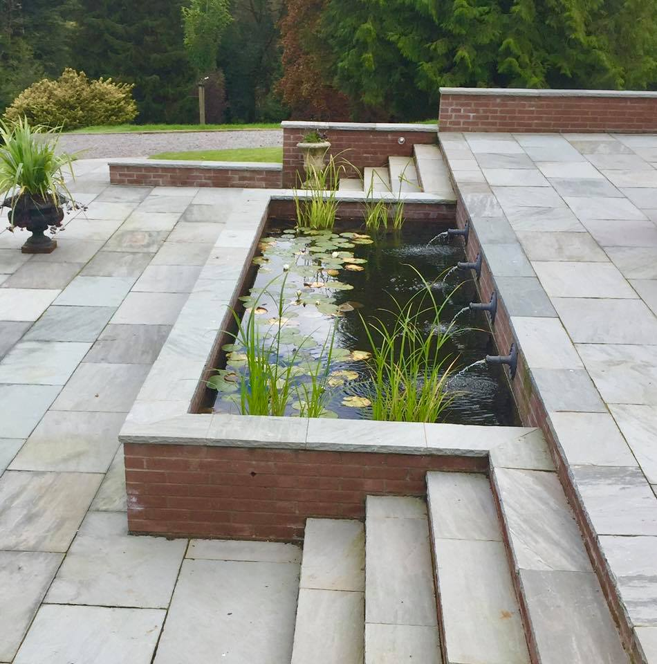 Lead water spouts raised pond at an art and crafts house landscaped near Glasgow