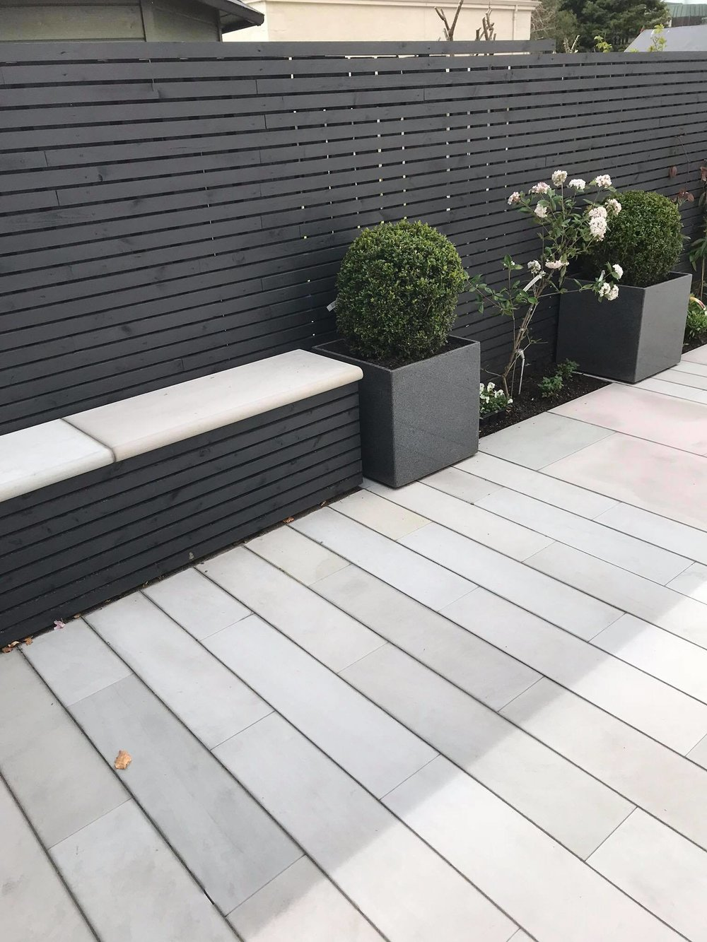 Gunmetal grey contemporary fence and seat facade for a courtyard garden in Eaglesham with smooth grey sandstone plank paving