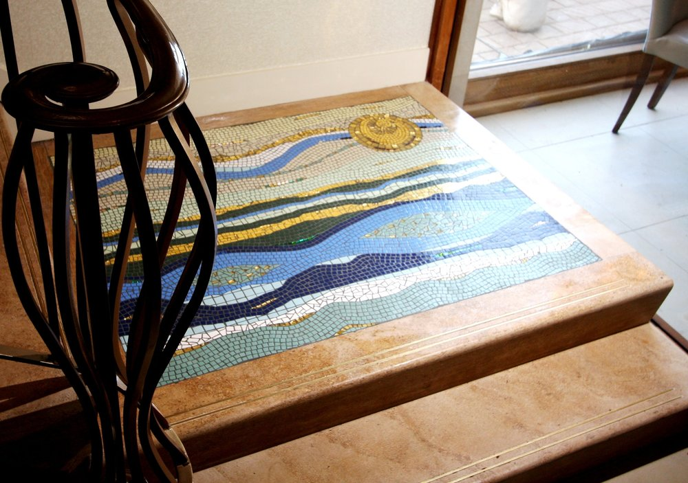 Quarter step of a turned staircase at Sheldrakes Restaurant, Heswall, Wirral. The design tries to imitate the beauty of the everchanging colours of the shoreline of the Dee Estuary on the banks of which the restaurant is situated, and the setting of the sun. Gold smalti, matt porcelain tile, gold leaf glass tile. Approx. 48ins. x 42ins.