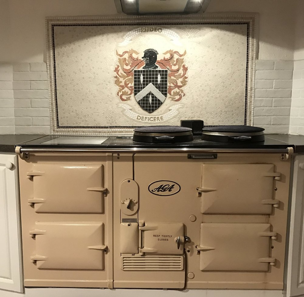 "Aga splashback. "" Jones "" family crest with an adaptation of the motto to read ""AUDEO DEFICERE"" or ""dare to fail"". Matt porcelain, gold glass, recycled gems, ceramic. 32ins. x 57ins."